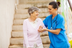 nurse assisting an elderly woman